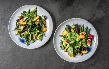 Fresh salad plates on black background