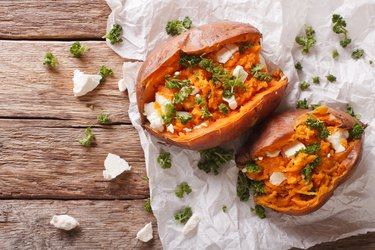 sweet potatoes baked with feta cheese and parsley on the table. horizontal top view