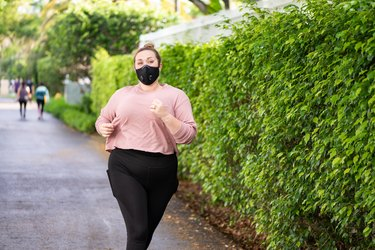 woman running with exercise face mask on sidewalk