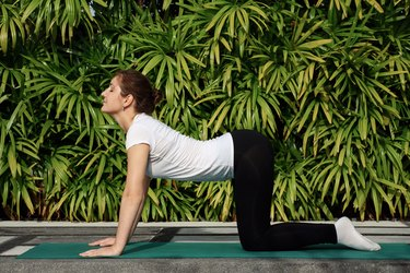 Fit woman practicing Cat-Cow pose on a green yoga mat outside
