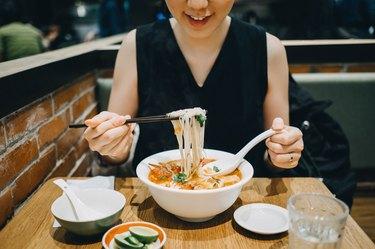 Asian woman eating soup noodles joyfully in restaurant