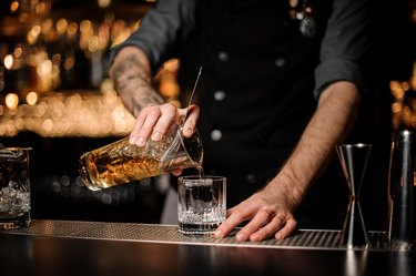 Bartender pours cocktail adding whiskey in glass