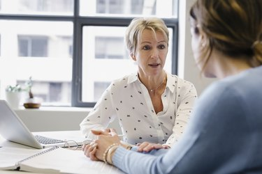 Businesswoman consoling colleague in office