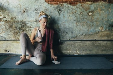 Woman in yoga clothes looking at fitness social media accounts on smart phone