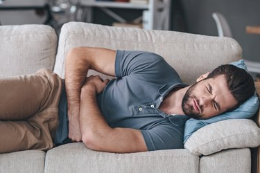 man lying on couch with severe abdominal pain after a meal