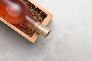 A bottle of Rose wine in a wood box