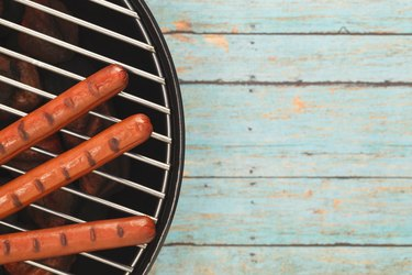 Three Hotdogs Grilling on Rustic Blue Picnic Table