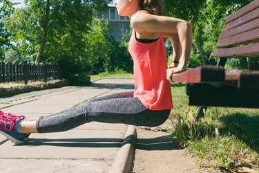 Woman in sportswear doing exercise on triceps on a bench