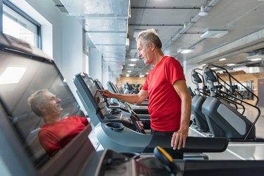 Senior man adjusting speed on treadmill, walking for an hour