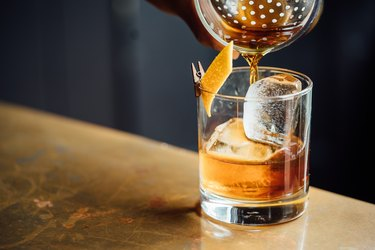 closeup of a cocktail shaker pouring into glass with dark alcohol, ice and orange peel