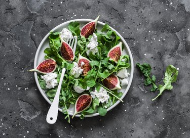 Figs, goat cheese, arugula salad on dark background, top view