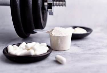 Creatine, Taurine capsules and a dumbbell. Bodybuilding food supplements on stone / wooden background. Close up. Copy space.
