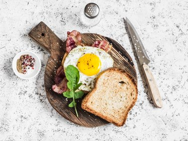Top view of toast with fried egg, bacon and arugula