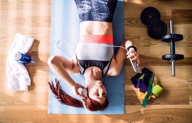 overhead photo of woman wearing headphones and scrolling through smartphone while working out at home with mat water bottle and dumbbells