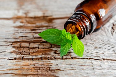 Small glass bottle on an old wooden background and fresh mint leaves, close up. Aromatherapy and spa ingredientes.