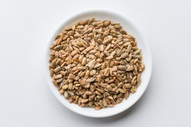 Close-Up Of Sunflower Seeds In Bowl Over White Background