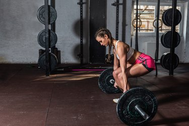 Young strong muscular fit girl with big muscles preparing for hard strength weightlifing or dead lift cross workout training with barbell weights in the gym real people
