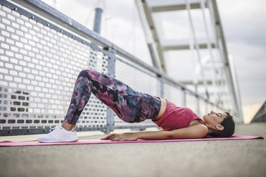 woman doing glute bridge exercise for rounder butt outside on pink yoga mat