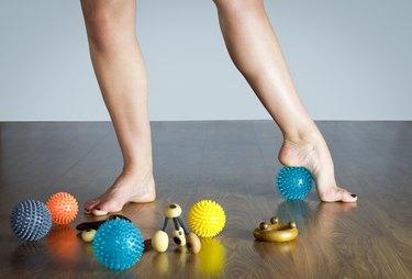ballet dancer massaging her foot with blue ball for massage