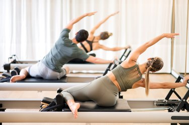 Group of people doing the mermaid pilates exercise on a pilates reformer