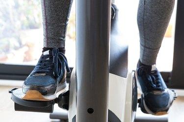 Unrecognizable Female Athlete Exercising on Stationary Bike at Home - Stock Photo