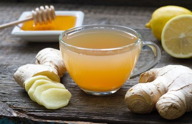 Ginger homemade tea infusion on wooden board with lemon, as an example of what to drink after hangover