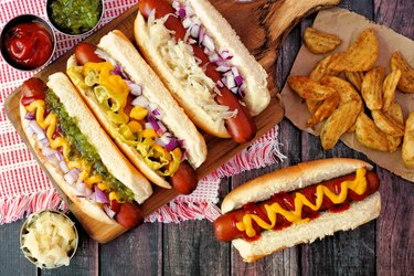Hot dogs with potato wedges, above scene on rustic wood