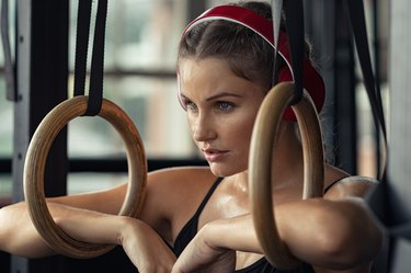 Woman listening to CrossFit music working out with rings