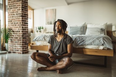 A man learning how to meditate in his bedroom at home