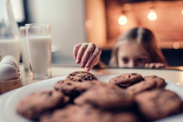 Little girl grabbing cookies in kitchen
