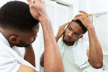 Young african man checking for thinning hair in mirror at bathroom