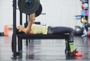 Woman lifting deadlift while lying on bench press in gym