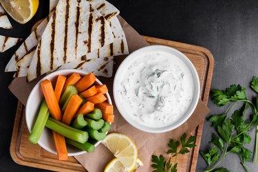 Yogurt Tzatziki sauce with parsley served with fresh carrot and celery sticks