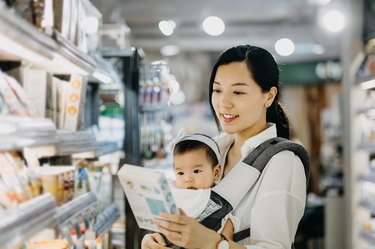 Beautiful Asian mother carrying cute baby girl shopping for organic baby food in grocery store
