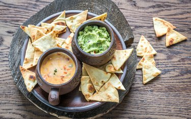 Bowls of guacamole and queso with tortilla chips.