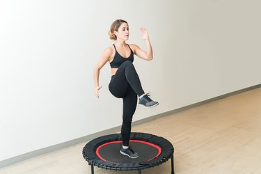 Woman doing a rebounder workout on a mini trampoline