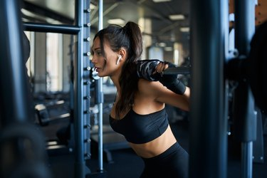 Woman doing squats in smith machine.
