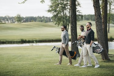 multiethnic golf players holding bags with golf clubs and walking on golf course