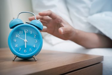 A person's hand hitting the snooze button on a blue alarm clock next to the bed
