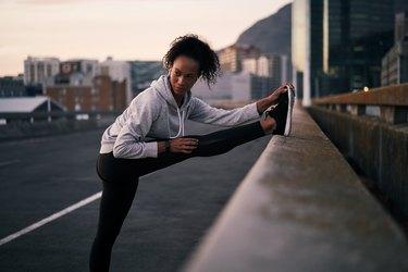 Woman stretching during run in urban area