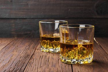 Whisky with ice in two glasses on a wooden background. Copy space. Food background