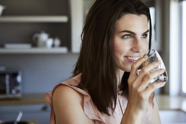 Beautiful woman in kitchen drinking a glass of water