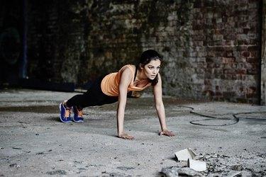 Woman doing pushups on concrete floor.