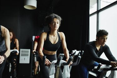 Woman riding stationary bike during fitness class in cycling studio