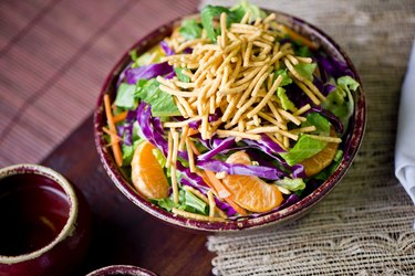 Salad with Mandarin oranges. Traditional Chinese salad with thinly sliced ribbon lettuce, red cabbage, carrots and fried crispy wonton noodles. Cuisine served on Chinese New Years.