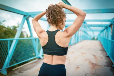 woman tying her hair in a ponytail before her workout