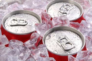 Close up of the tops of three soft drink cans in ice