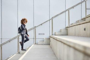Businesswoman using smart phone on steps