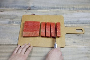Chef chopping a fresh raw red salmon fillet with kitchen sharp knife
