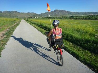 Woman on recumbent bicycle pedals Colorado Bear Creek Lake Park